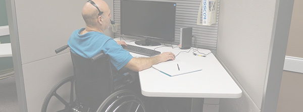 Man in Wheelchair at Computer Desk Working